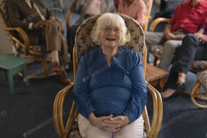 Front view of happy senior woman with hand clasped, sitting and looking at camera in nursing home