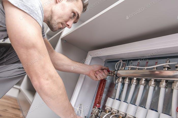 Männer Einstellen der Wohnungswärme an den Zentralsystemventilen