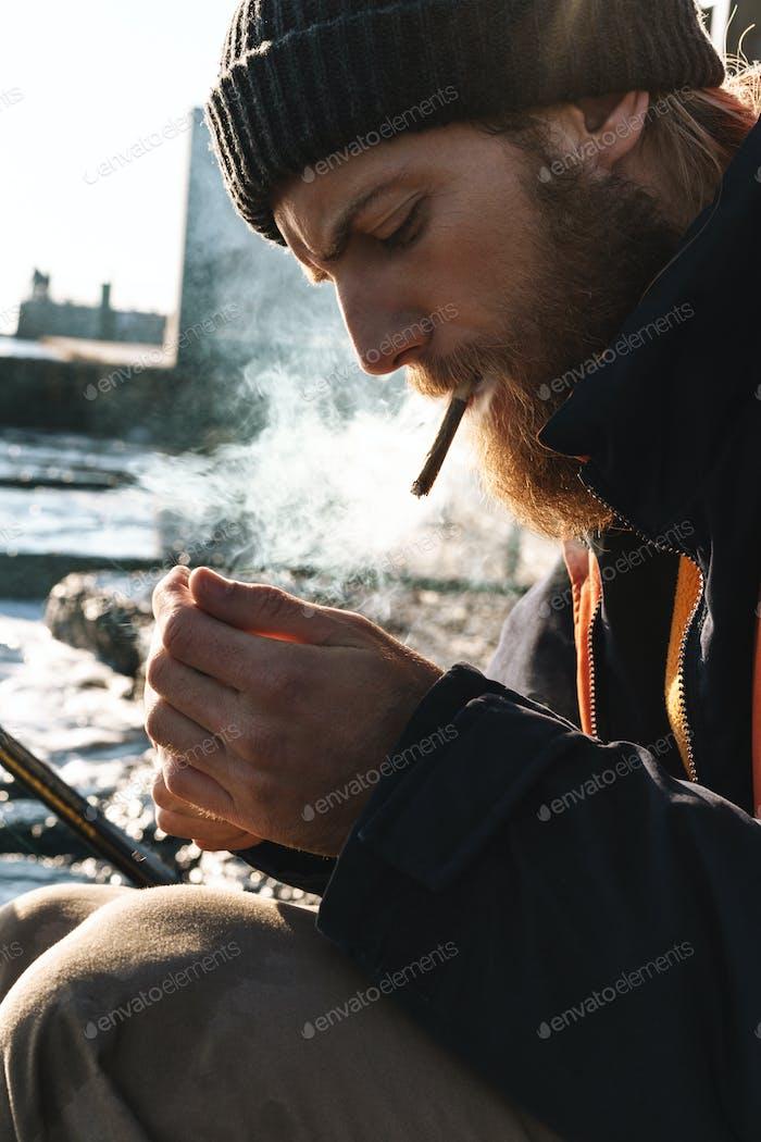 Handsome young man fisherman wearing coat and hat at the seashore smoking.