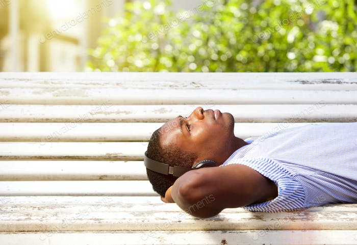 Young black man lying on a park bench with headphones