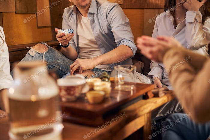 Young man spending time with friends in tea house