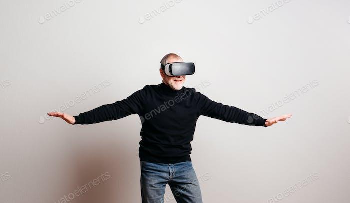 Porträt eines fröhlichen älteren Mannes mit VR-Brille in einem Studio