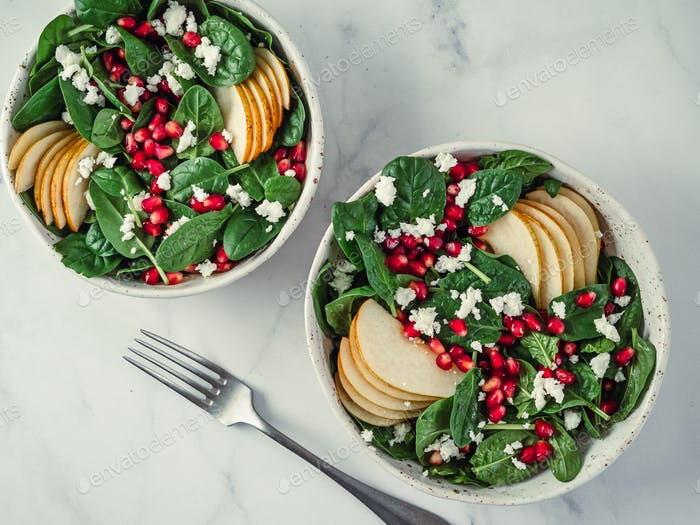 salad with spinach, pear, pomegranate and cheese