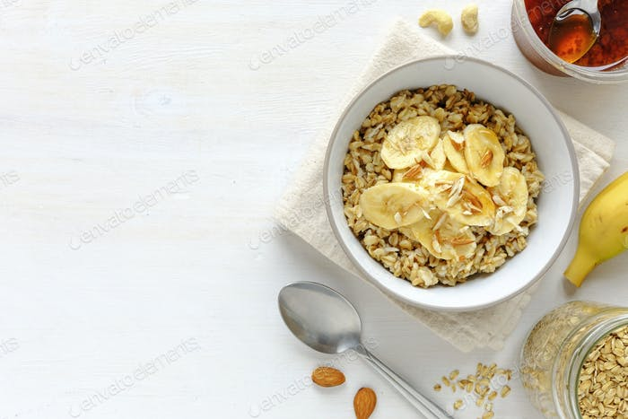 Bowl of oatmeal with banana against white table