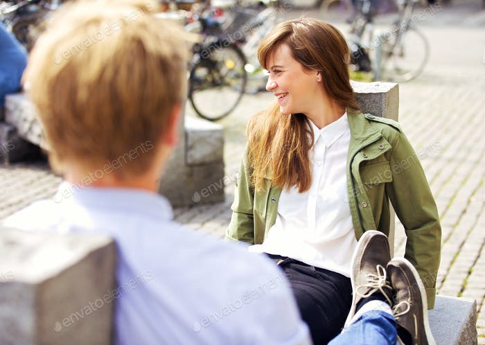 Woman Sitting on a Park Bench Together with Boyfriend