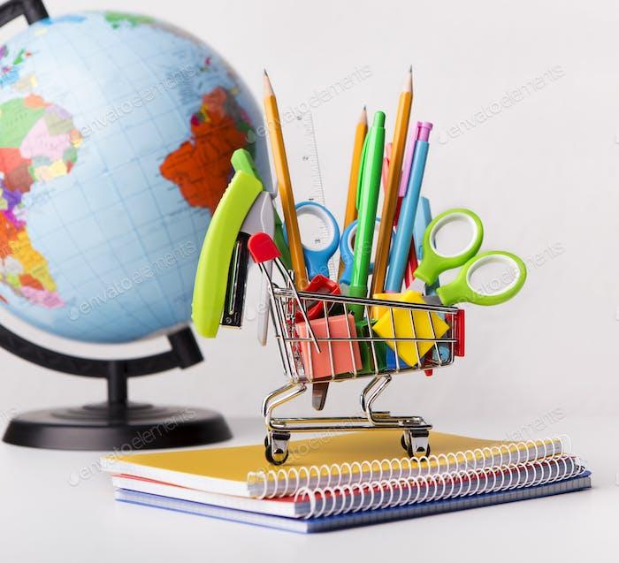 Einkaufswagen mit Schulpapier mit Weltkugel auf weiß