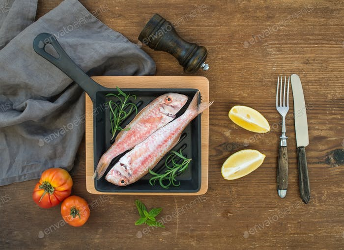 Raw uncooked Red Mullet fish in a cooking pan with rosemary, lemon and garlic