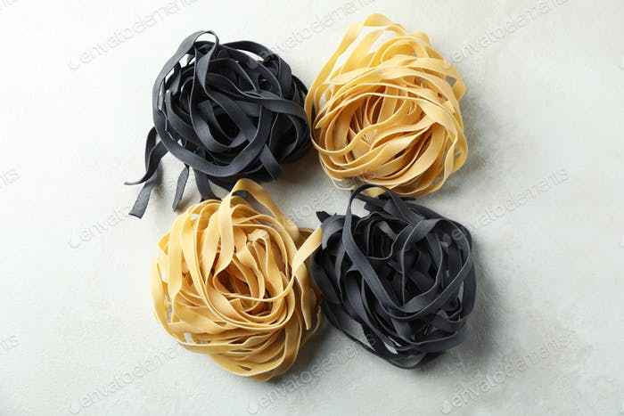 Black and white uncooked pasta on white textured background