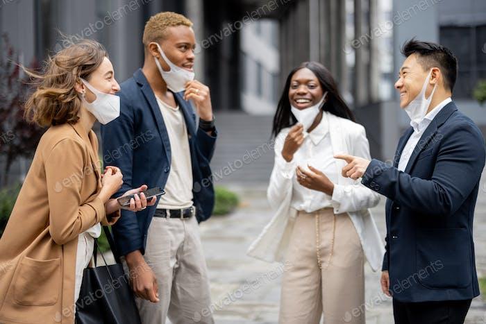Business team taking off medical masks and talking