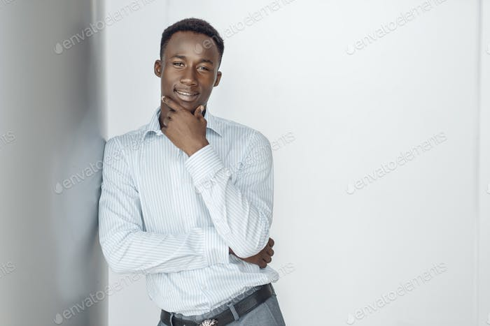 Ebony businessman poses in office building