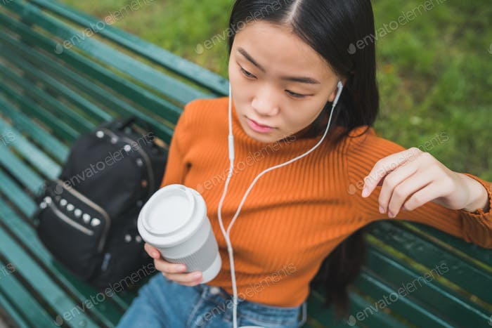 Asian woman listening to music.