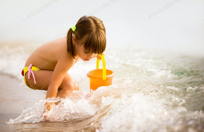 Small girl playing with toys in sea water edge