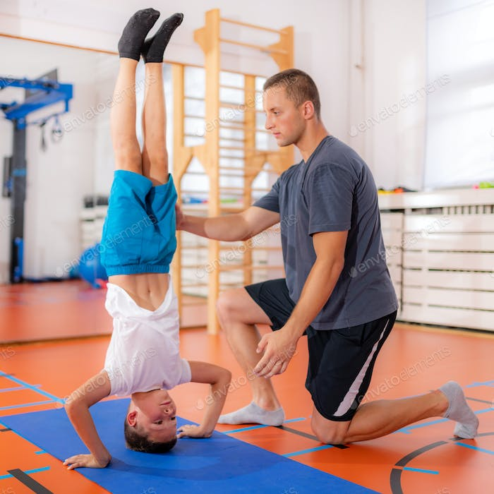 Physical activity for children, child doing a hand stand with trainer