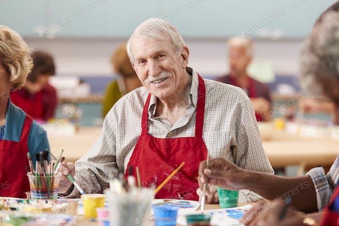 Porträt von Rentner Senior Man Teilnahme Kunst Klasse in Community zentrum