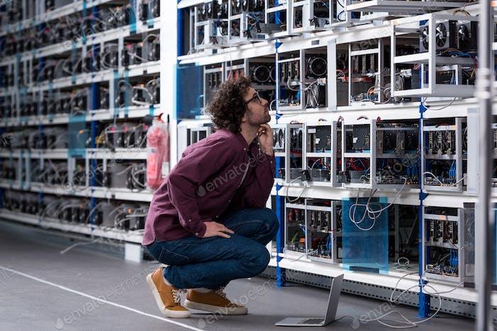 joven ingeniero informático sentado en el suelo y mirando a la granja minera de criptomonedas