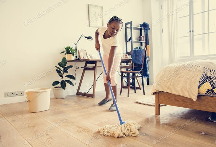 Young teen girl sweeping up the floor