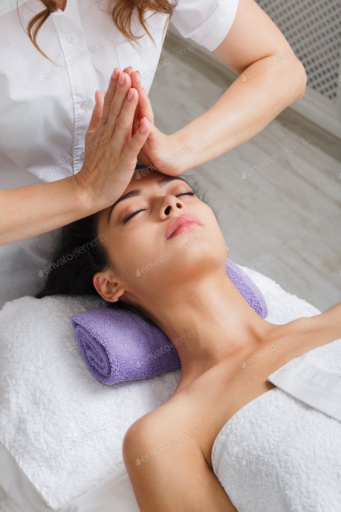 Woman beautician doctor make head massage in spa wellness center