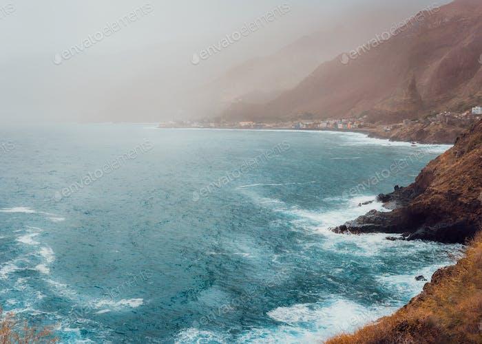 Paul Pombas, Santo Antao Cape Verde. Bluff volcanic coastline covered by sunlight penetrates dust