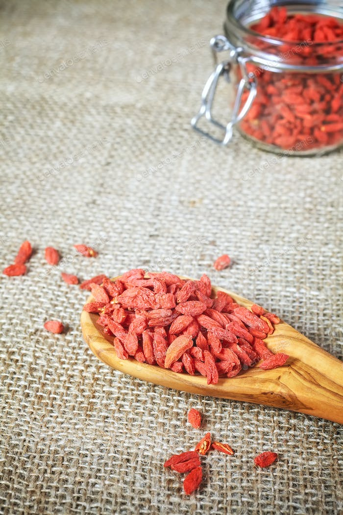 Dried goji berries on a wooden spoon and linen background.
