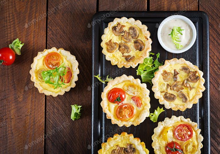 Mushrooms, cheddar, tomatoes tartlets on wooden background. Mini pies.