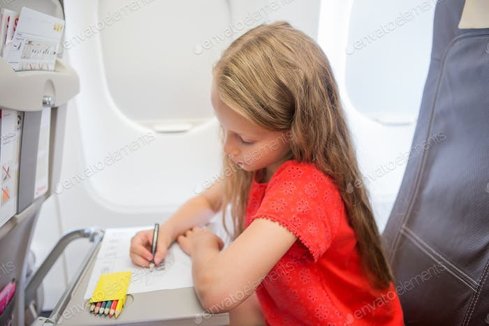 Adorable little girl traveling by an airplane. Kid drawing picture with colorful pencils sitting