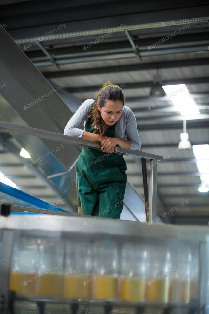 Female factory worker inspecting production line
