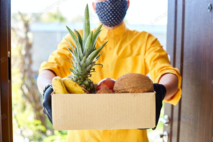 Courier man delivery box with exotic fruits food, contactless delivery.