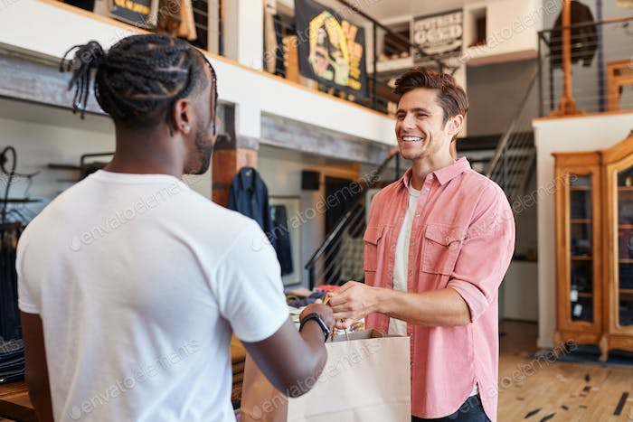 Sales Assistant Handing Purchases To Male Customer In Fashion Store