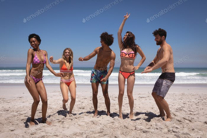 Happy group of multi ethnic friends dancing together on beach in the sunshine against ocean waves