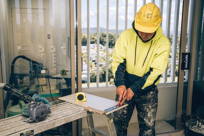 Mann Markierung Markierungen mit Bleistift auf einer Fliese geschnitten werden. Verlegung von keramischen Bodenfliesen, Hausrenovierung