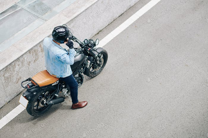 Motorcyclist adjusting helmet