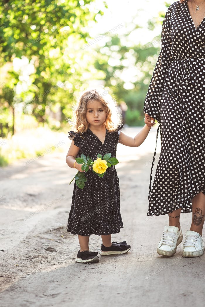 A little girl is holding her mom by the hand