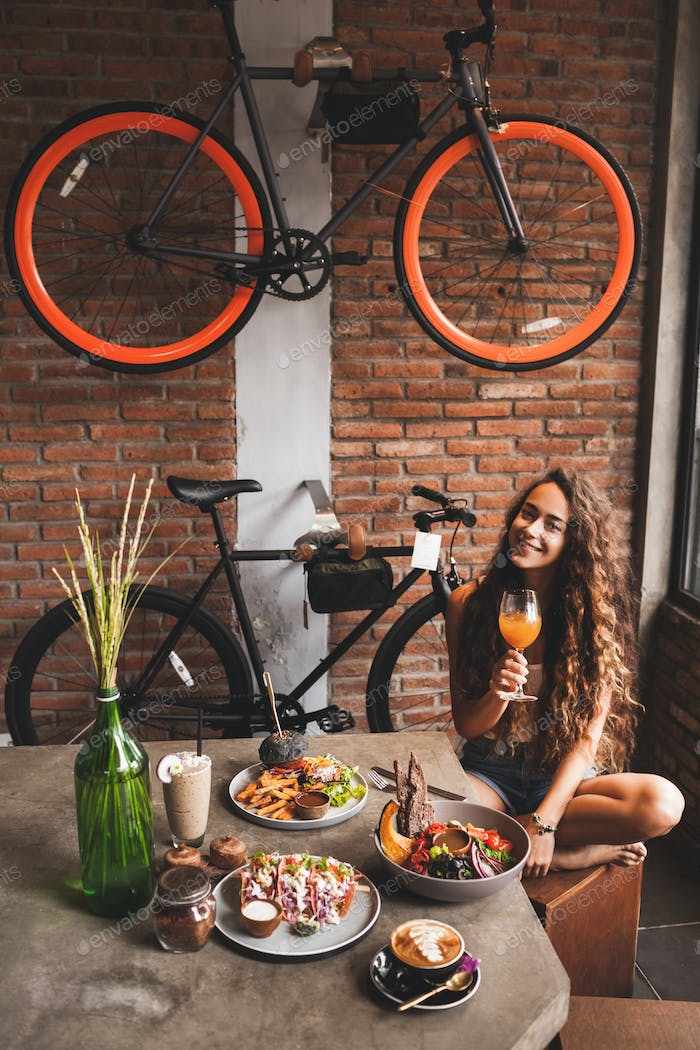 Woman enjoying fresh organic vegetarian food and glass of kombucha in hipster style cafe