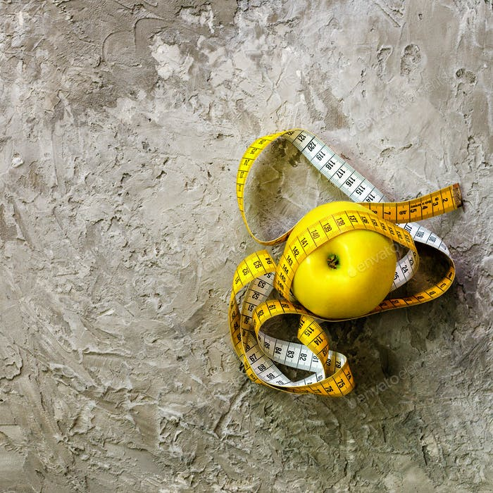 Yellow apple with measuring tape on concrete background. Top view