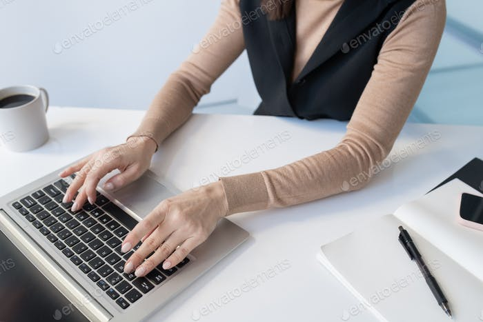 Hands of young businesswoman over laptop keypad during work
