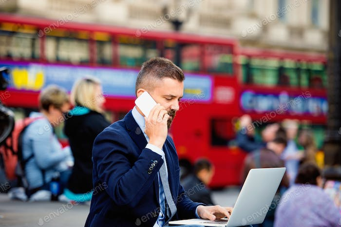 Manager with laptop and phone against  Londons red double-decker buses