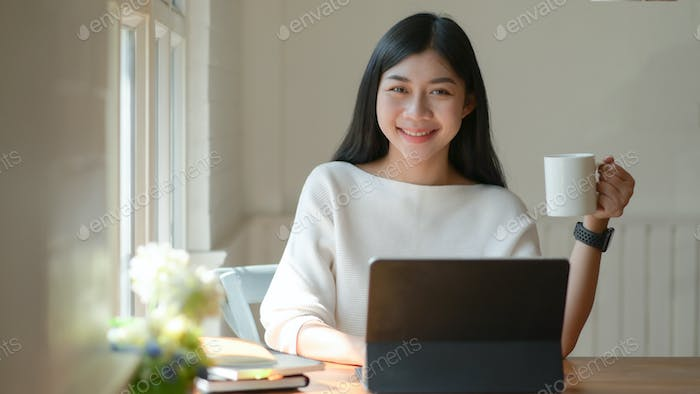Young girl holds a coffee cup and uses a laptop. She looked at the camera and smiled happily.