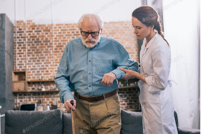 Doctor helping elder male patient with cane