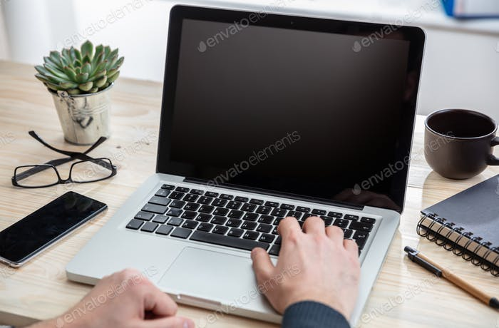 Laptop with black blank screen on a wooden desk
