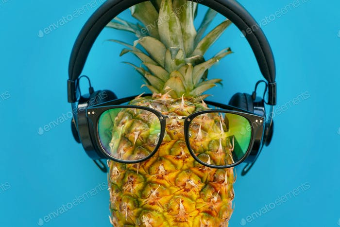 Stylish pineapple in sunglasses and headphones on blue paper background