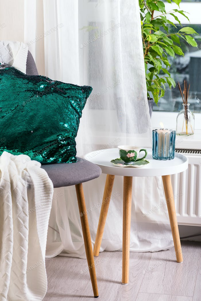 a cup of herbal tea on a table, a knitted wool blanket , green sequin pillow on a chair and candle