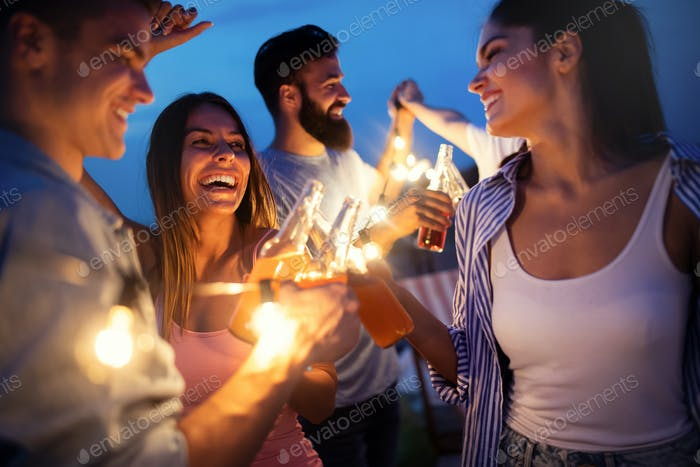 Happy friends with drinks toasting at rooftop party at night