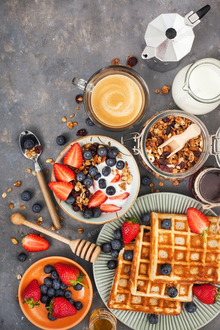 Breakfast table with cereal granola, milk, fresh berries, coffee