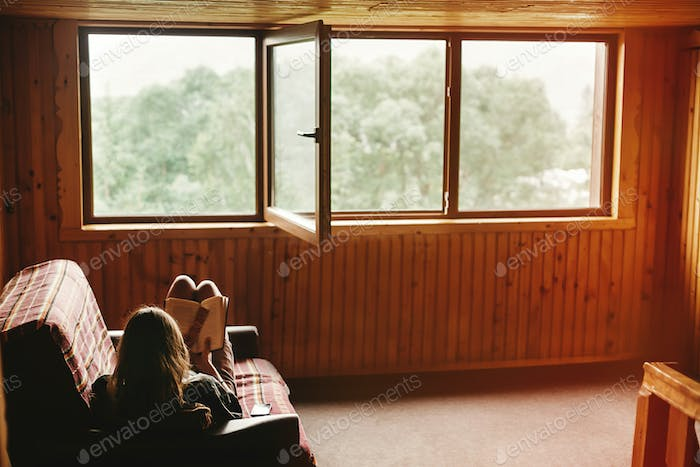 Hipster woman sitting on coach and reading book in wooden cottage