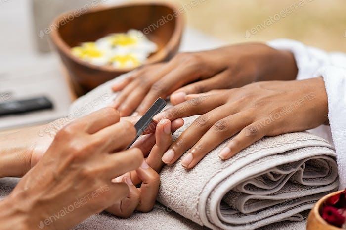 Kosmetikerin Datei Nägel zu einer schwarzen Hand
