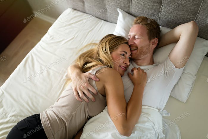 Beautiful couple lying in bed in morning