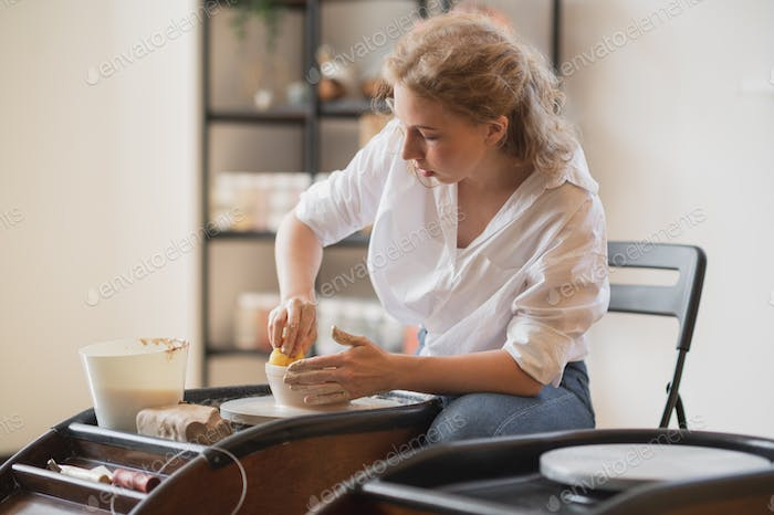 Woman working on potters wheel making dishes with their own hands. Close-up photo of dirty hands
