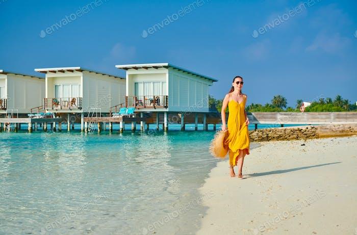 Woman in dress running on tropical beach