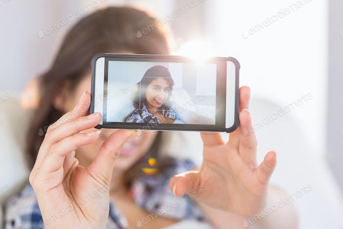 ziemlich Brünette nehmen ein selfie auf couch zu Hause in die Wohnzimmer