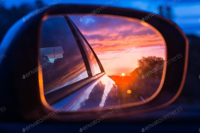 Fiery sunset as seen on the car's side mirror